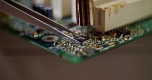 Smoking soldering iron on a computer motherboard closeup. Micro chip soldering stock footage