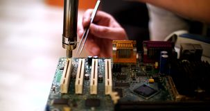 Smoking soldering iron on a computer motherboard closeup. Micro chip soldering stock video