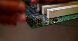 Smoking soldering iron on a computer motherboard closeup. Micro chip soldering stock video footage