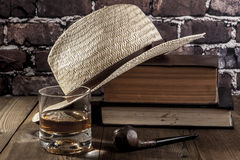 Smoking Some Books. Hat and books on brown wood table Stock Photo