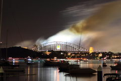 Smoke over Sydney harbor bridge at night. Long exposure image of Sydney harbor with pall of smog wandering off and fast moving boats on their way home. At Stock Photo