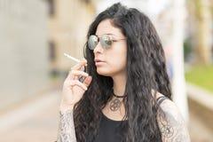 Smoking tattooed sensual beautiful woman, outdoor. Royalty Free Stock Photo