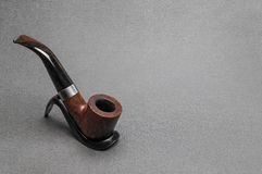 Smoking tobacco pipe bent type wooden. Briar. Briar Irish tobacco smoking pipe bent type made of heather on a stand on a gray background royalty free stock images