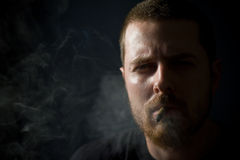 Smoking tough man in the shadow Royalty Free Stock Photo
