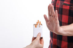 Smoking is a very bad habit for me. Close up of male hand refusing to smoke. The human hand is holding a pack of cigarettes and proposing it to man. Isolated and Royalty Free Stock Images