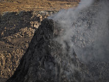 Smoking volcanic pinnacle close to Erta Ale volcano, Ethiopia. Smoking pinnacle in the Erta Ale volcano area. The lava flow formed incredible waves and patterns Stock Photos