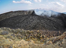 Smoking volcanic pinnacle close to Erta Ale volcano, Ethiopia. Smoking pinnacle in the Erta Ale volcano area. The lava flow formed incredible waves and patterns Stock Image