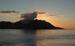 Smoking volcano at sunset. A smoking volcanic island silhouetted against the sunset. The clouds and sky are orange and yellow. These are reflected in the still stock images