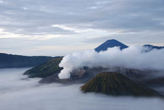 Smoking volcano. Tenger massif in Java island, Indonesia at dawn and under fog blanket. On the photo there are three volcanoes - Bromo smoking, Semeru highest