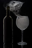 Smoking wine glass and bottle Stock Photo