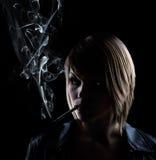 Smoking woman on black background Stock Image