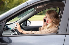 Smoking woman  driving a car and speaking on the phone Stock Photos