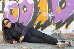 Smoking woman at the graffiti brick wall Stock Images