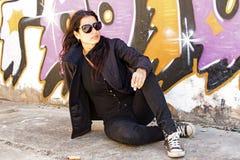 Smoking woman at the graffiti brick wall Stock Photos