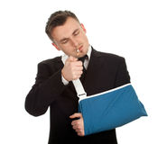 Smoking young businessman with broken hand Royalty Free Stock Image