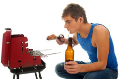 Smoking young man with beer grilling chiken Royalty Free Stock Photography
