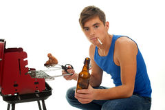 Smoking young man with beer grilling chiken Stock Image