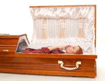 Smoking young woman in brown coffin Royalty Free Stock Photos