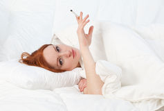 Smoking young woman in white bedding Stock Photo
