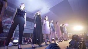 Smokingowy przedstawienie wybieg, grupa fachowi modele w eleganckie projektant suknie chodzi wzdłuż pasa startowego w rzędzie prz zbiory wideo