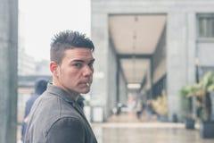 Smokng hermoso joven del hombre en las calles de la ciudad Imagen de archivo libre de regalías