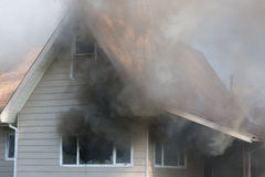 Smoknig House. Thick smoke engulfs a home, foreshadowing the blazing destruction to come Stock Image