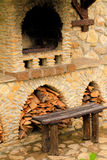 Smoky antique brick oven outdoor with firewood and a bench Stock Photo