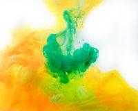 smoky background with green and orange paint flowing in water royalty free stock images
