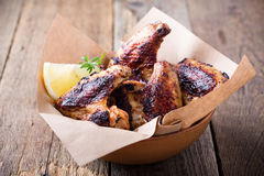 Smoky barbecued chicken wings. In ceramic bowl on wooden ready to eat royalty free stock photography