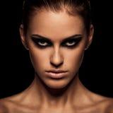 Smoky eye. Closeup portrait of a serious lady with smoky eye makeup Royalty Free Stock Image