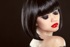 Smoky eyes makeup closeup. Black bob hairstyle. Sexy red lips. Brunette girl with shiny glossy short hair over dark background Stock Photos