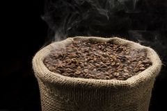 Smoky, hot coffee beans in the sack. Sack full of still hot, freshly roasted coffee beans with the smoke rising in the air Royalty Free Stock Photography