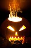 Smoky Jack-o-lantern. Smoky Halloween pumpkin Jack-o-lantern and small pumpkins in foreground Stock Image