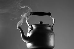 Smoky kettle. A teapot on the table, from the nozzle there is smoke, representing steam, black and white Royalty Free Stock Photography