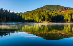 Smoky lake reflect forest mountain and blue sky Stock Images