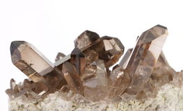 Smoky Quartz crystals. A cluster of smoky Quartz crystals on a white background. This specimen was found in Switzerland Stock Image