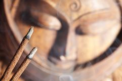 Smoldered sandal-wood incense. And Buddha image background Stock Photos