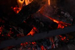 Smoldering ashes of a bonfire. Fire flame in a brick barbecue. Smoldering ashes of a bonfire. Incandescent orange and red embers texture. Dark background. Fire Stock Photography