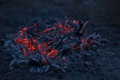 Smoldering ashes of a bonfire. Incandescent orange and red embers texture. Dark background Stock Photo