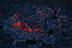 Smoldering ashes of a bonfire. Incandescent orange and red embers texture. Dark background Royalty Free Stock Photo