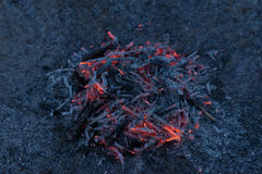 Smoldering ashes of a bonfire. Incandescent orange and red embers texture. Dark background Royalty Free Stock Images
