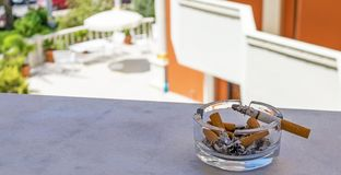 Smoldering cigarette lying on the ashtray. Ashtray and cigarette against the background of the garden. stock images