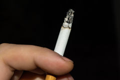 Smoldering cigarette sandwiched between male fingers Stock Images