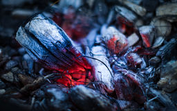 Smoldering ember in the fire. Dark smoldering ashes in the fire Royalty Free Stock Image