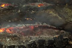 Smoldering embers of fire. Smoldering firewood in a fire close up Royalty Free Stock Photography