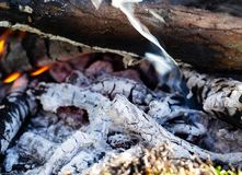 Smoldering embers of fire with log in smoke, close up royalty free stock photography