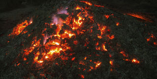 Smoldering fire. Ash heap with smoldering embers at night Stock Image