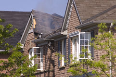 Smoldering Roof. Fire damaged smoldering roof of a non descript brick house Stock Photo