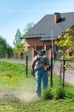 Smolensk, Russia - possono 12, 2018: l'uomo con una falciatrice da giardino manuale falcia l'erba fotografia stock libera da diritti