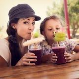 Smoot ягод счастливой девушки ребенк и смешной эмоциональной матери выпивая стоковые фотографии rf